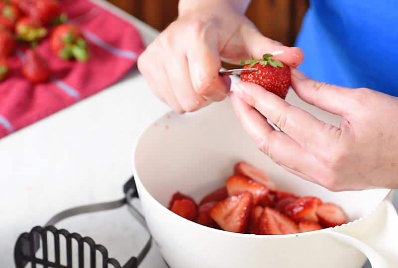 stemming strawberries with a paring knife for easy strawberry freezer jam
