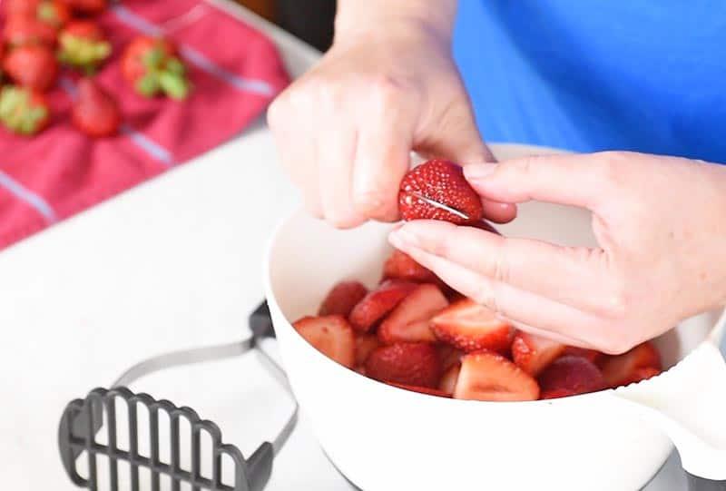 slicing strawberries in half for easy strawberry freezer jam