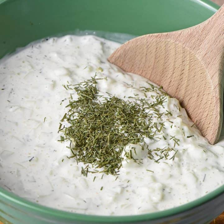 easy recipe for tzatziki sauce in green bowl with wooden spoon