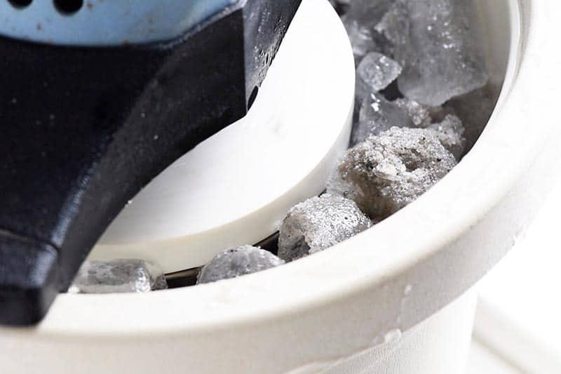 ice cream maker with ice, rock salt, and vanilla ice cream inside