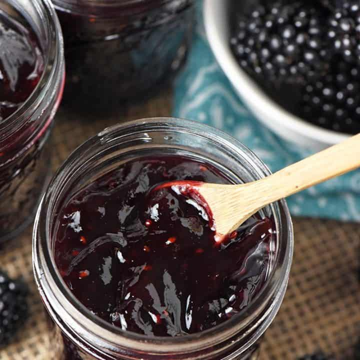 close up jar of homemade blackberry jam with tiny wooden spoon and fresh blackberries