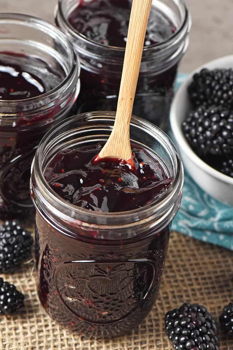 blackberry jam without pectin in half pint jar with small wooden spoon
