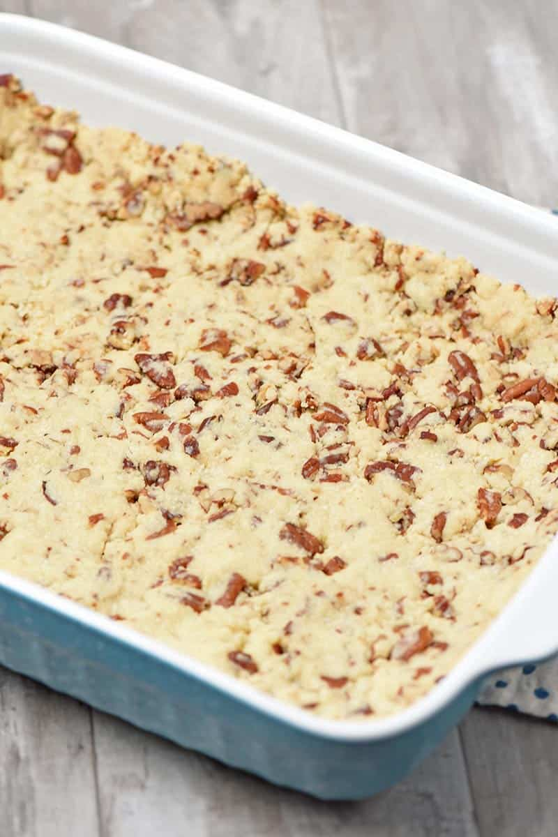 press in nutty pie crust, made with butter, flour, and pecans in blue baking dish