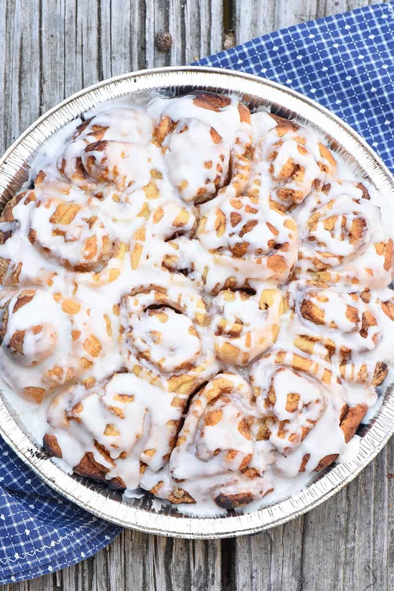 frosted cinnamon rolls in a foil pie plate on a wooden surface with a blue cloth