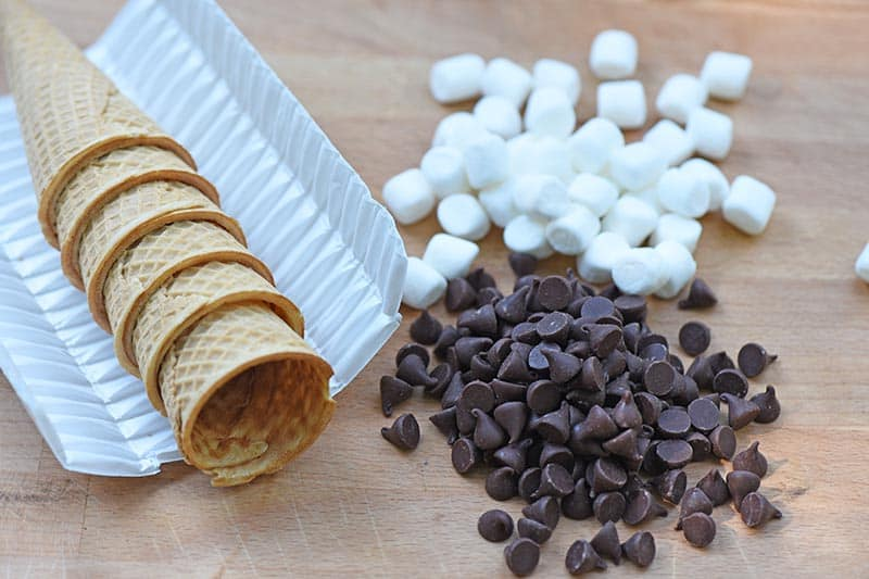 ingredients for campfire s'mores recipe, including sugar cones, Ghirardelli chocolate chips, and mini marshmallows on a cutting board