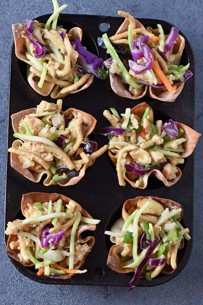 Asian chicken salad recipe made in baked wonton cups in a cast iron muffin tin