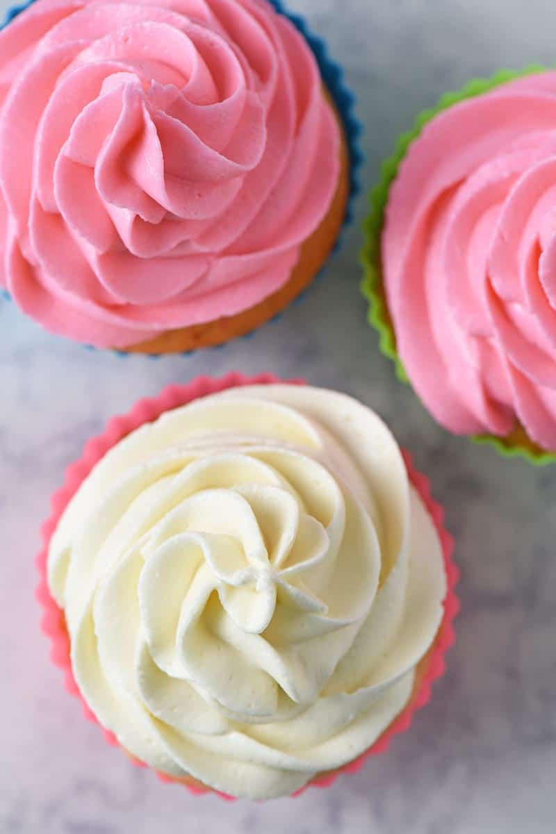 best buttercream frosting for piping, buttercream icing for piping on cherry chip cupcakes on white marble countertop