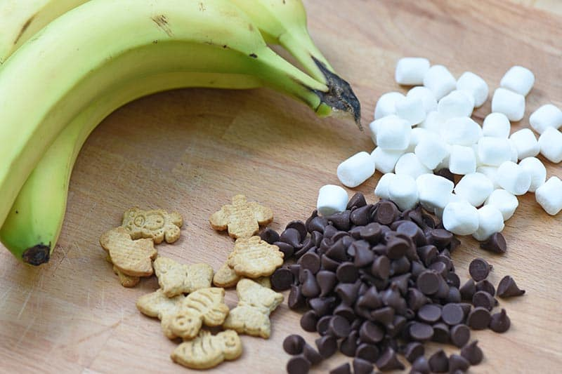 ingredients for banana boats s'mores on a cutting board, including chocolate chips, mini marshmallows, Teddy Grahams, and bananas