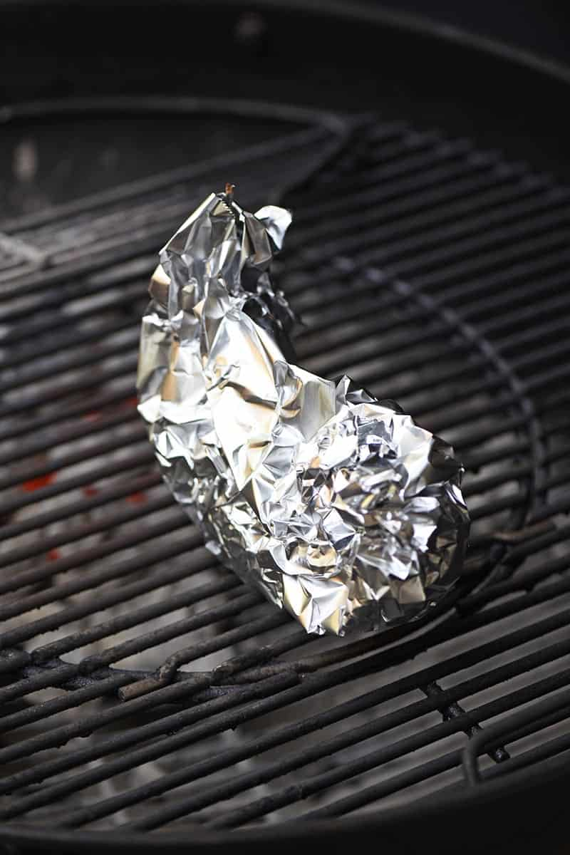 banana boats wrapped in aluminum foil, cooking on the grill