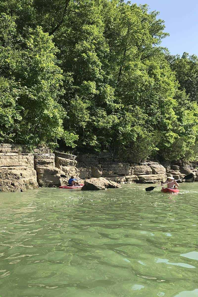 paddling kayak through boulders sticking up out of Beaver Lake