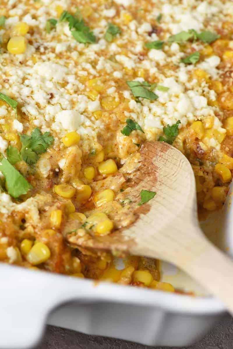 wooden spoon in Mexican corn casserole with cilantro on top