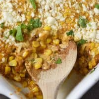 wooden spoon dishing up Mexican corn casserole from white casserole dish