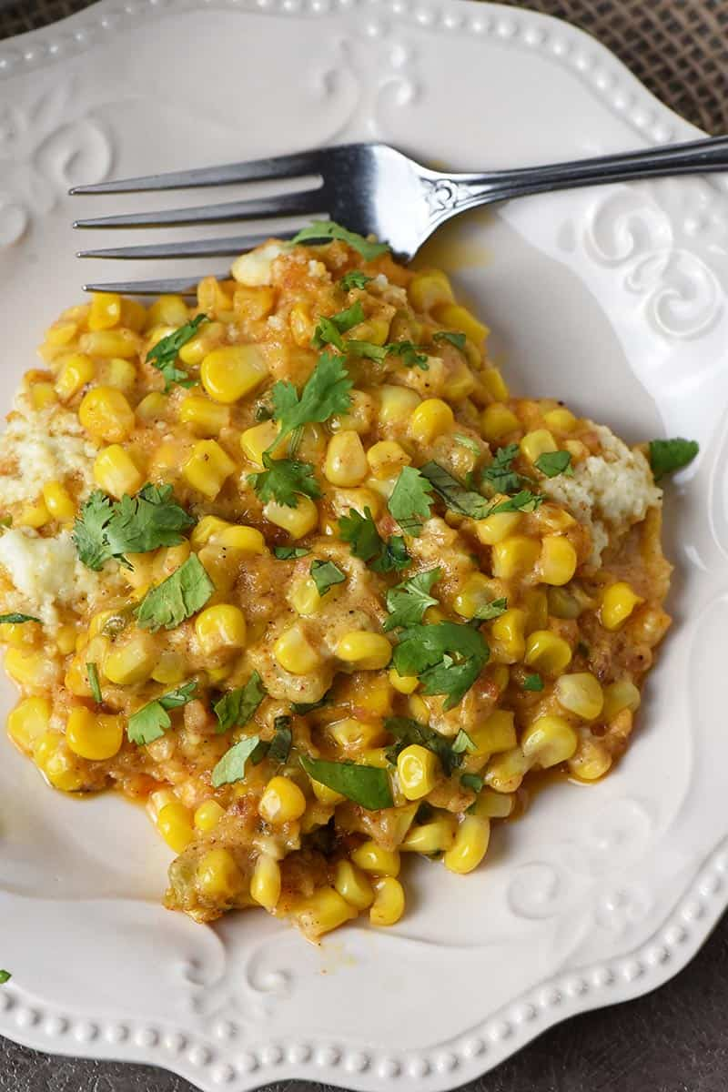 Mexican corn casserole dished out on white Pioneer Woman plate