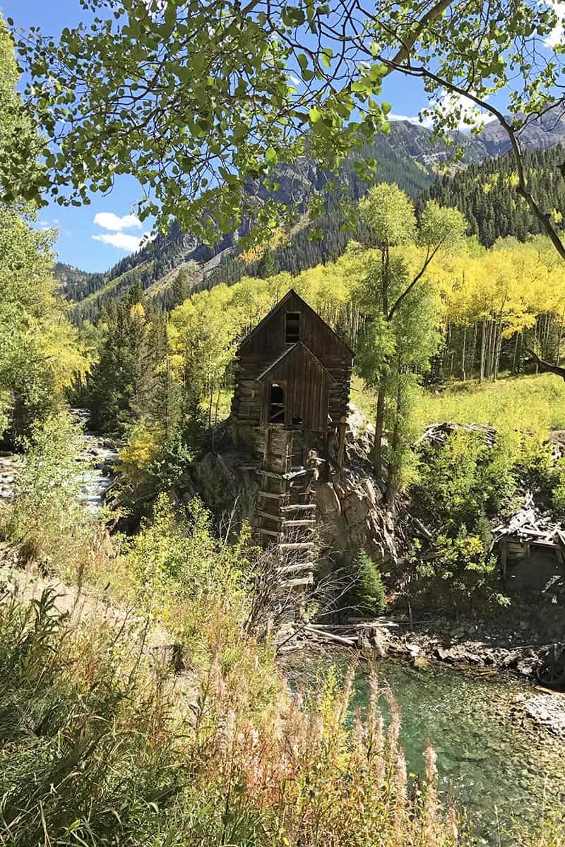 ghostly Crystal Mill in Colorado surrounded by golden yellow aspen trees and mountains