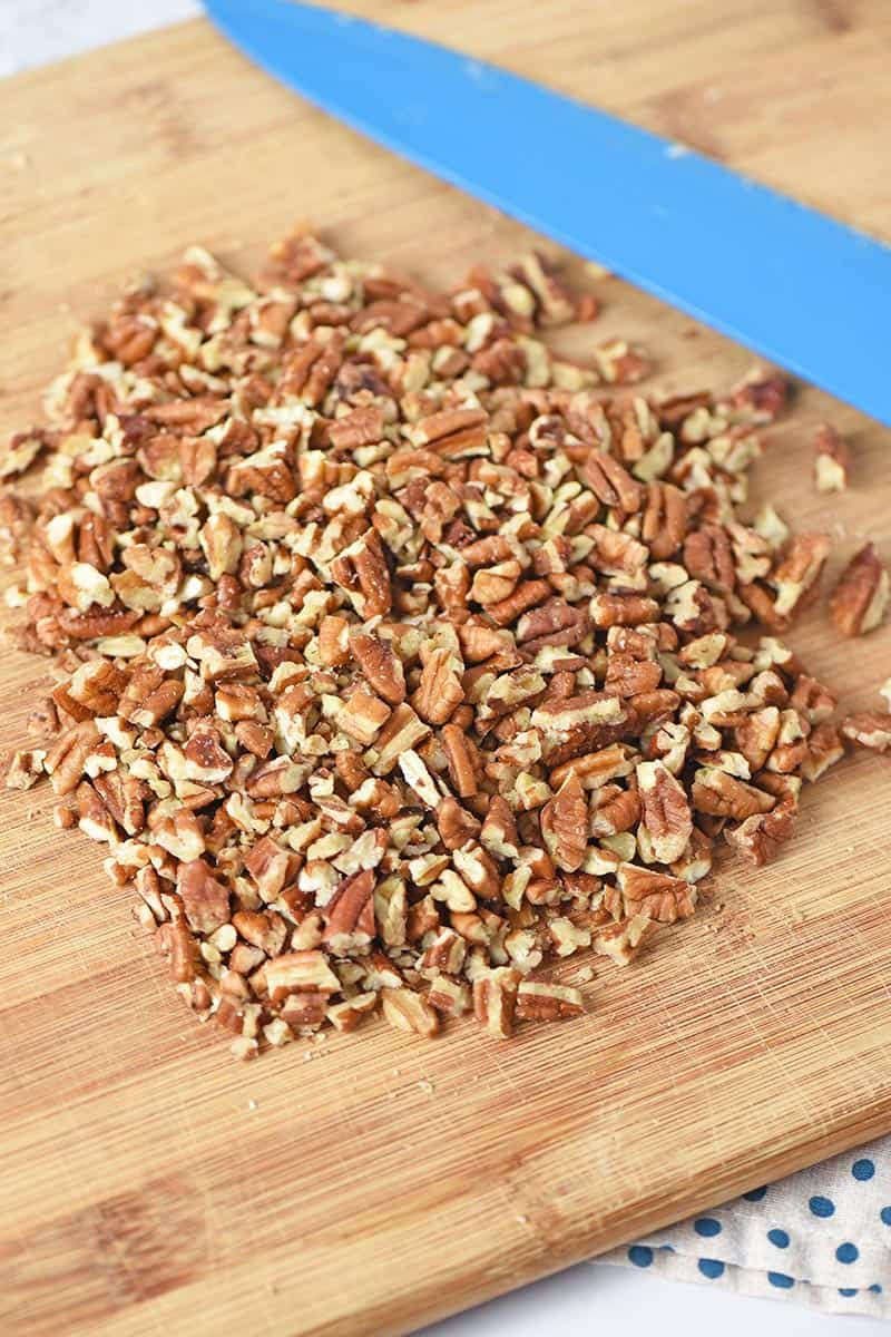 chopped pecans for pie crust recipe on cutting board with knife