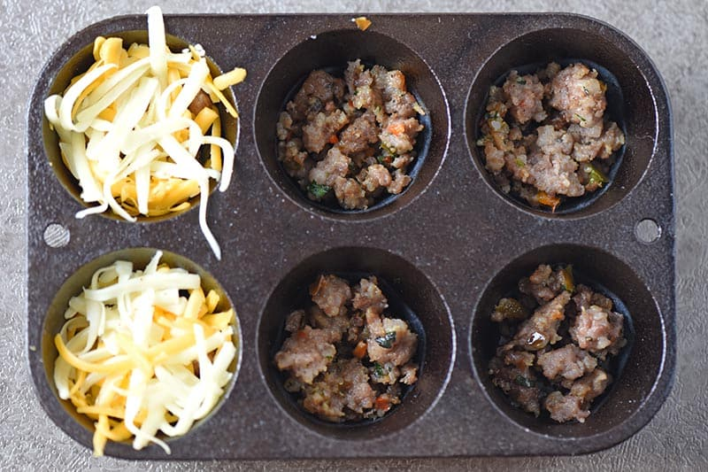 layering sausage and cheese for sausage egg muffins in cast iron muffin pan