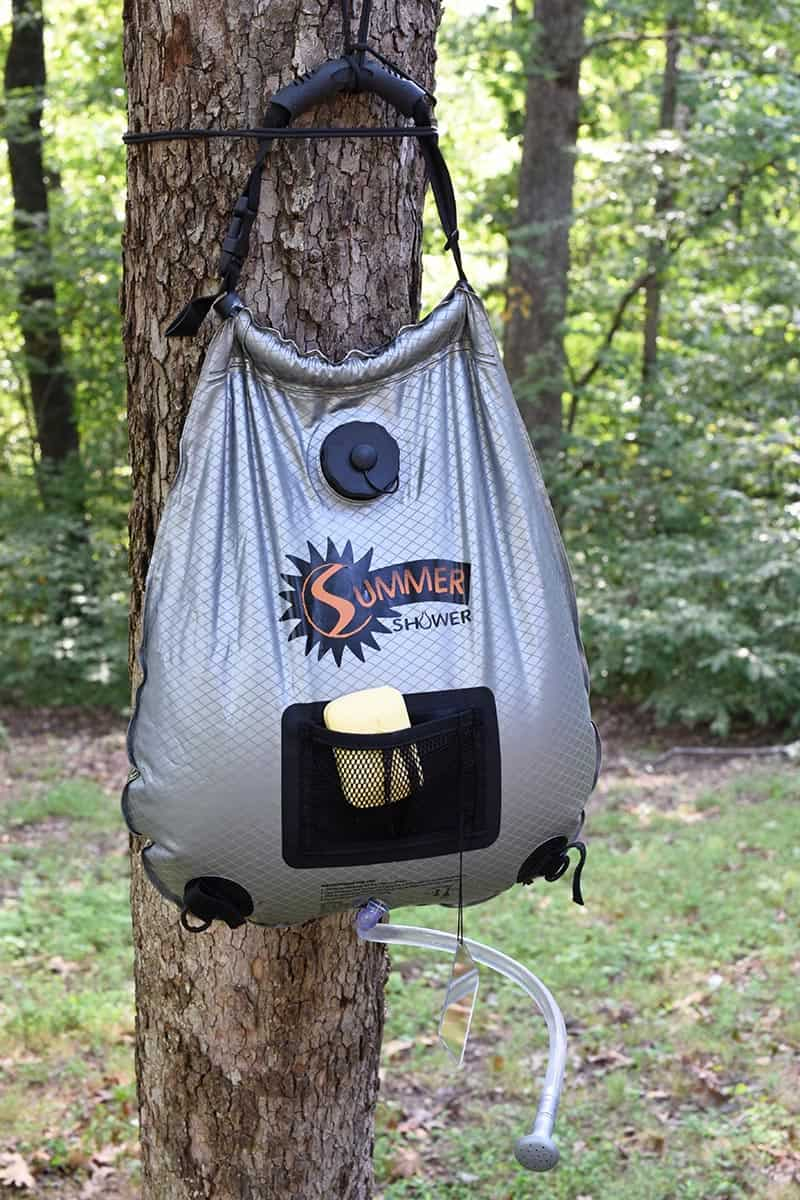 hang outdoor camp shower bag on tree, somewhere where you won't hurt any vegetation, where you'll ultimately leave no trace