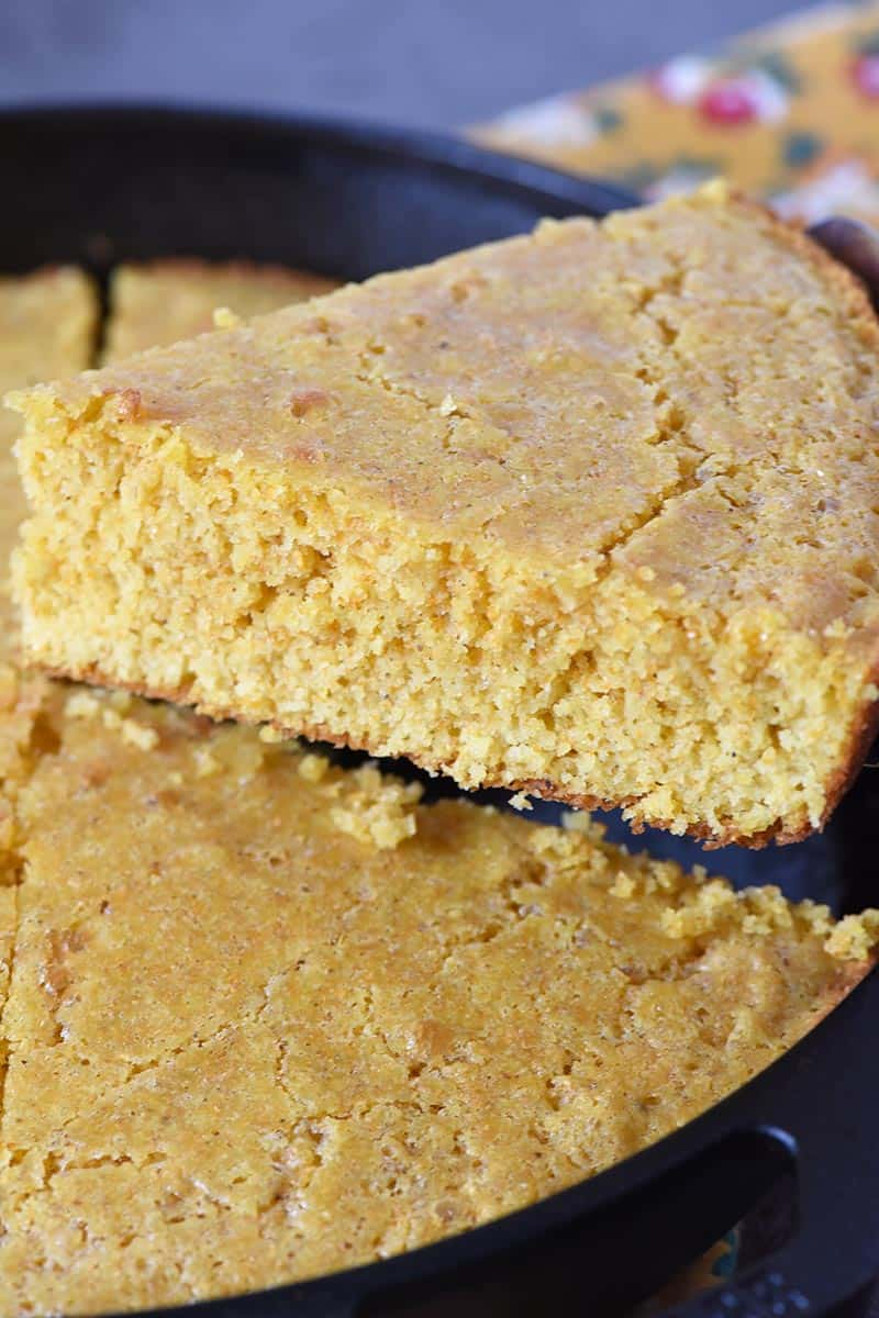 slicing buttermilk cornbread in cast iron skillet