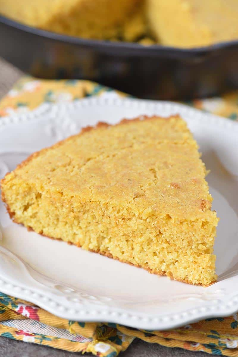 slice of buttermilk cornbread on white pioneer woman plate