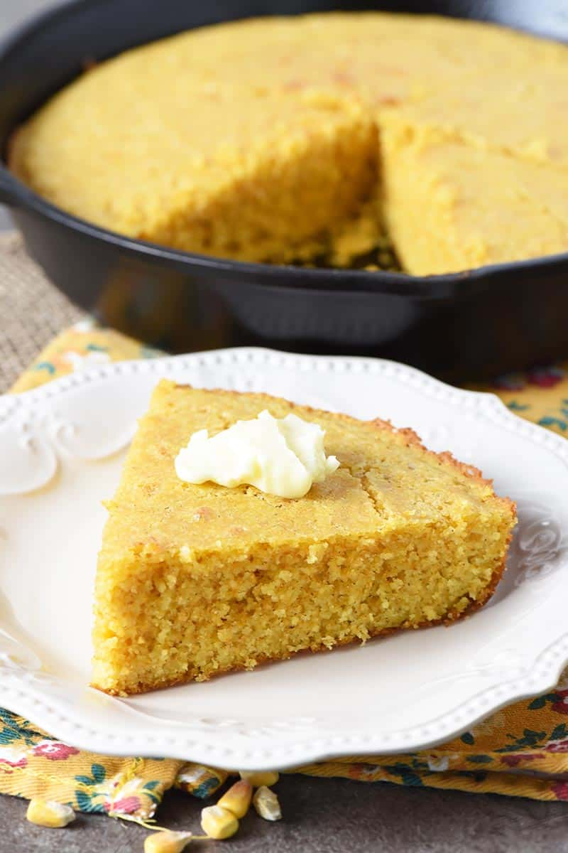 Slice of buttermilk cornbread with butter on white plate