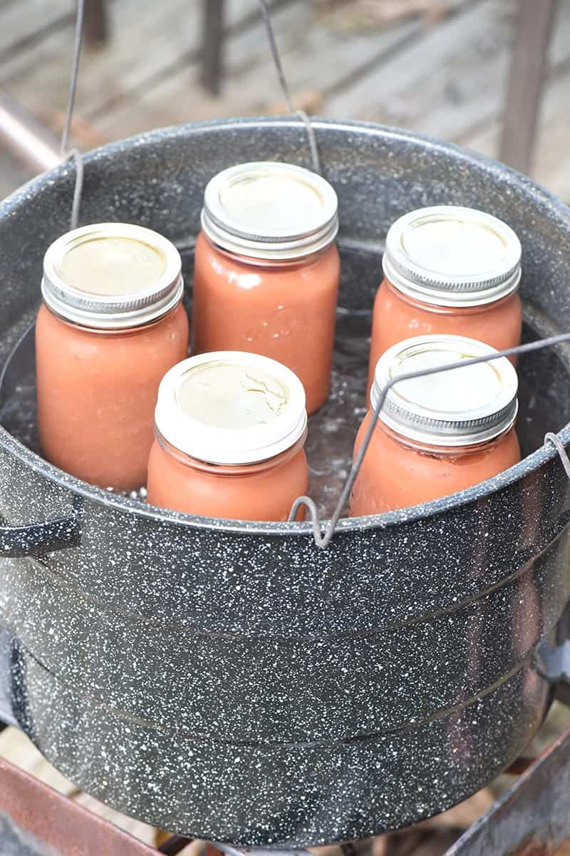 canning jars of applesauce in water bath