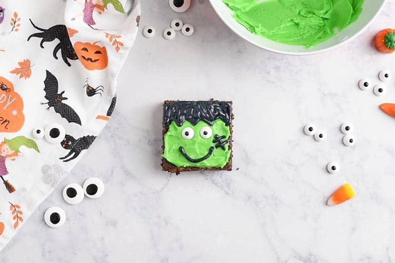 decorating Frankenstein Halloween Brownies with candy eyeballs, black icing smile, and stitches
