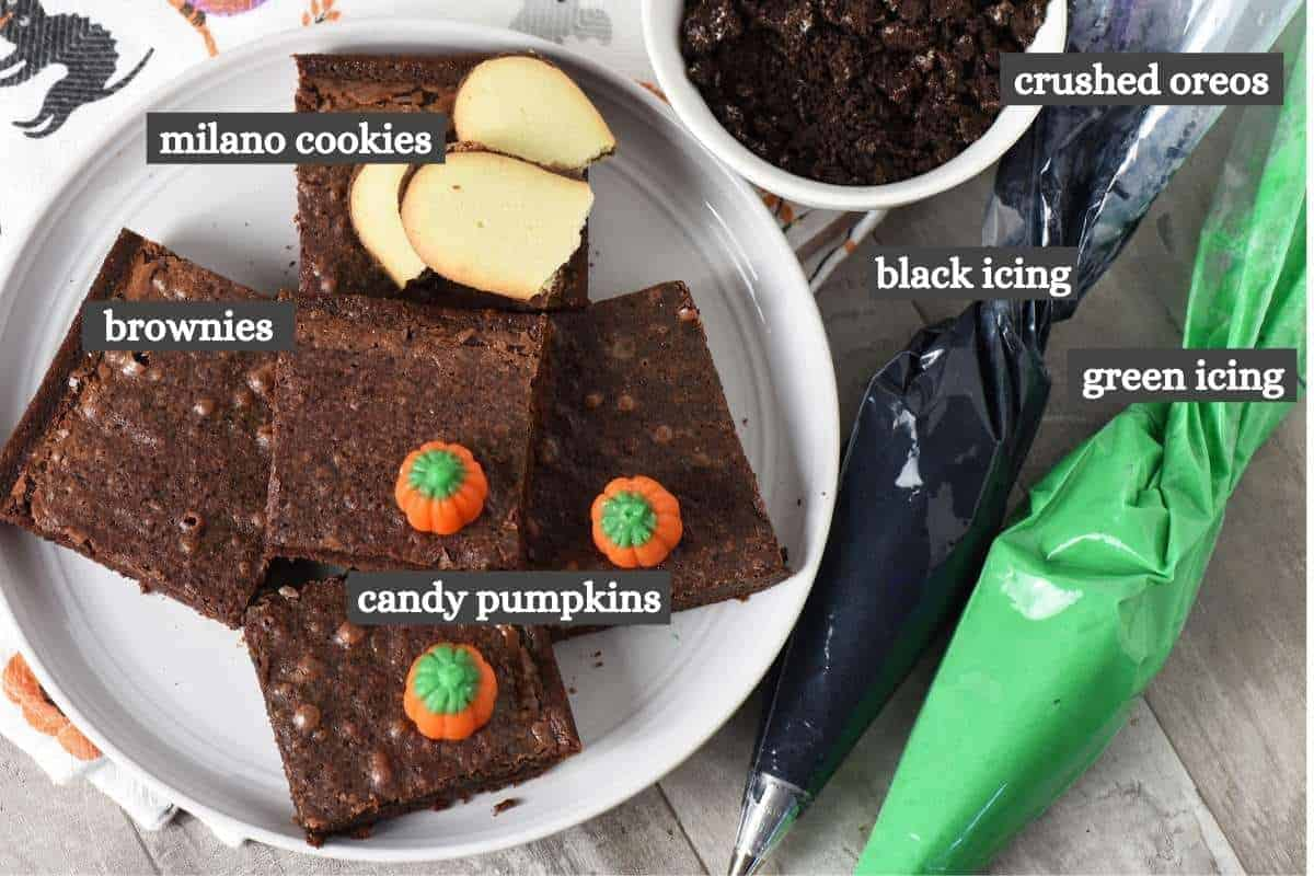Graveyard brownies ingredients on wooden countertop, including brownie mix brownies, Milano cookies, green and black icing, Oreo Cookies, and candy pumpkins