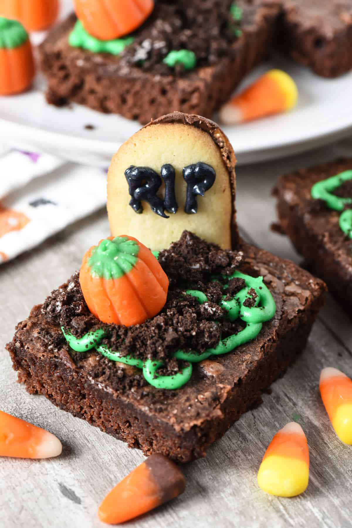 spooky graveyard brownies with Milano Cookies as gravestones, Oreos as dirt, green icing, and candy pumpkins