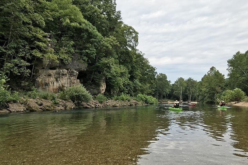 kayaking past a bluff on the Jacks Fork River