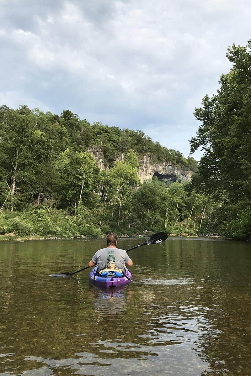 kayaking the Jacks Fork River, looking up at a bluff side cave