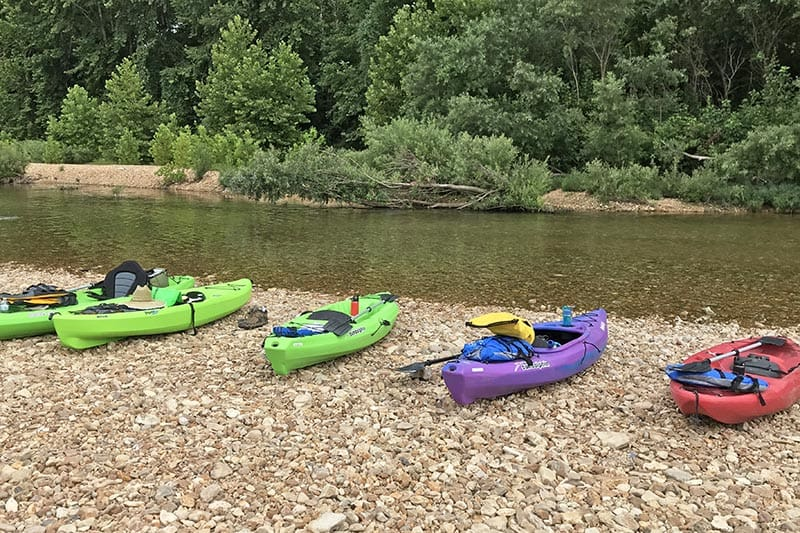 kayaks getting ready to launch on the banks of the Jacks Fork River at the Burr Oak day use area at Alley Spring