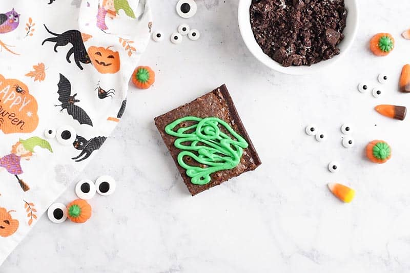 green icing for grass and pumpkin vines on graveyard halloween brownies