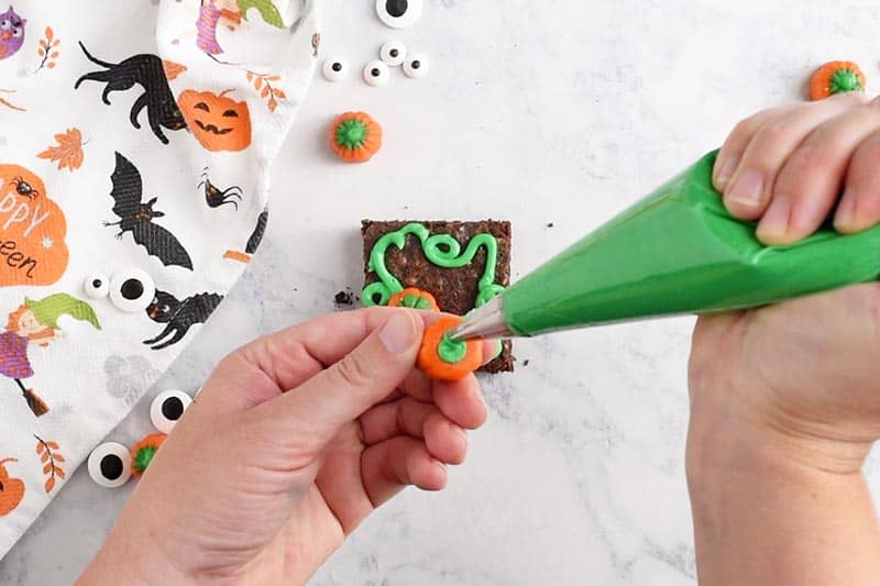 adding green icing to mellowcreme pumpkin for pumpkin patch Halloween brownies