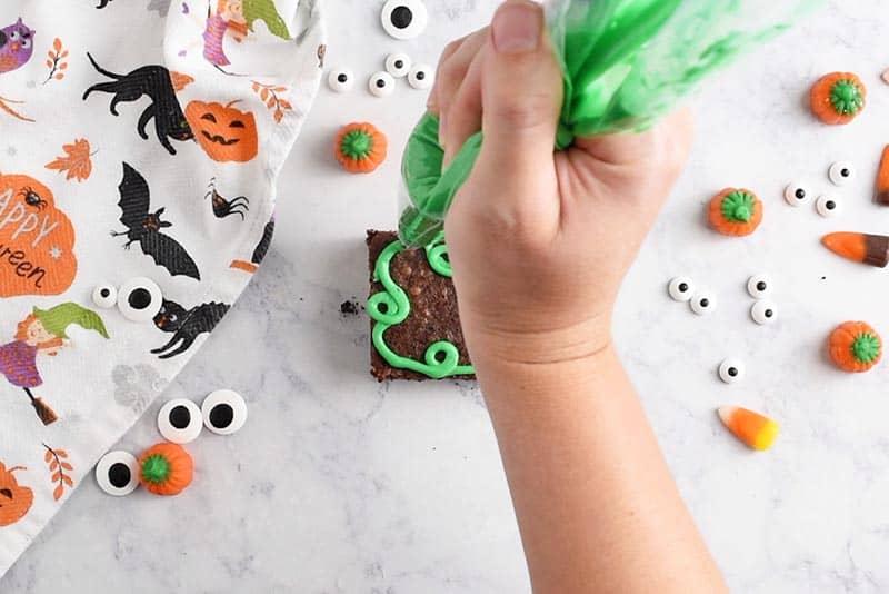 swirling pumpkin vines with green icing onto pumpkin patch halloween brownies halloween treats