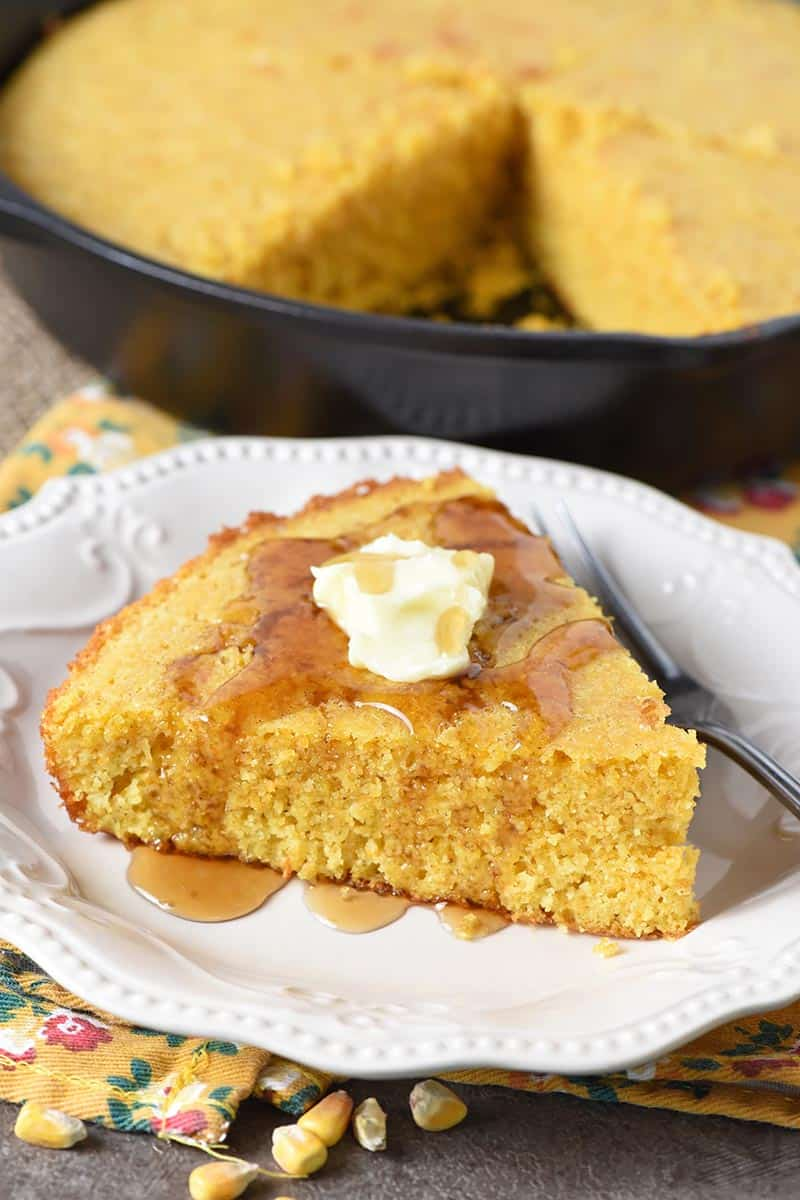 homemade buttermilk cornbread with butter and maple syrup on white plate