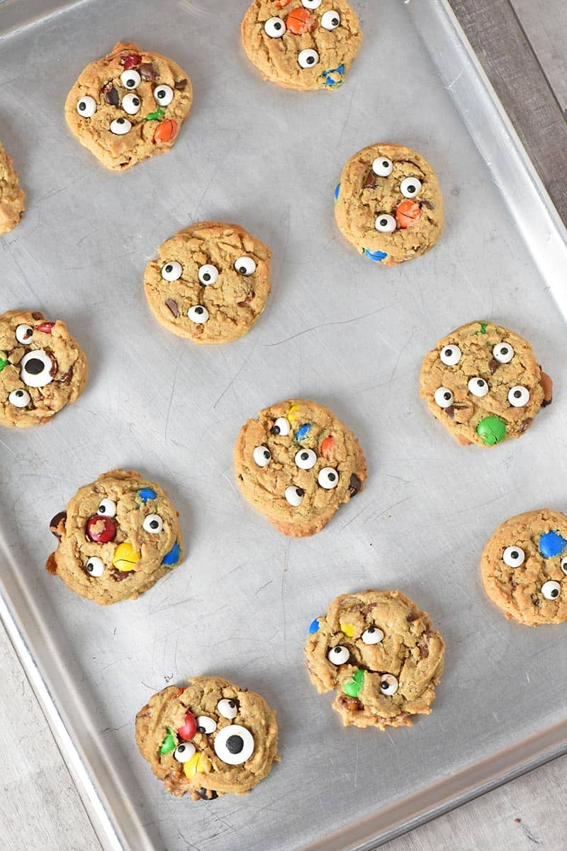 decorating Halloween cookies like monster cookies with candy eyeballs on a cookie sheet