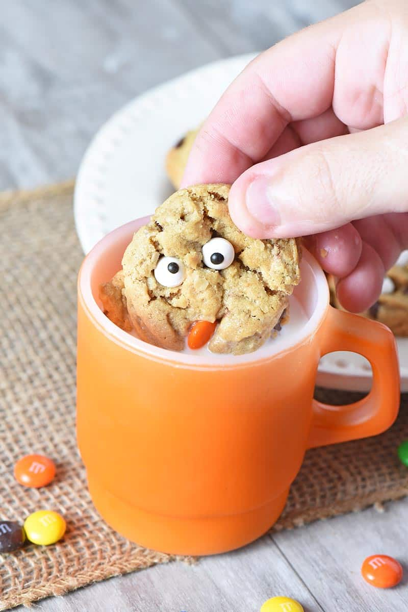 dunking monster cookies in milk in orange Fire King mug