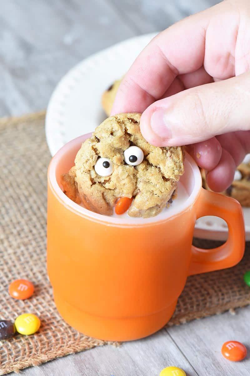 dunking monster cookies in milk in orange Fire King mug