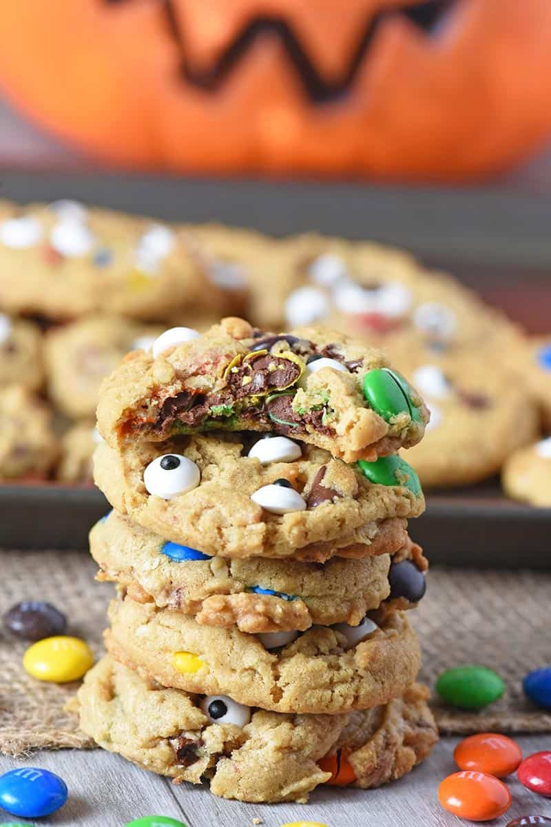 stack of monster cookies with bite taken out of Halloween cookie