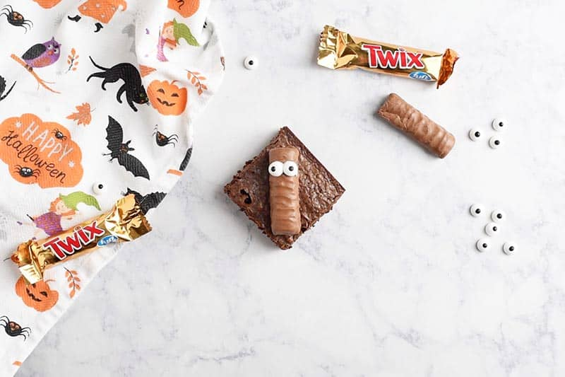 add candy eyeballs to Twix bar for mummy Halloween brownies