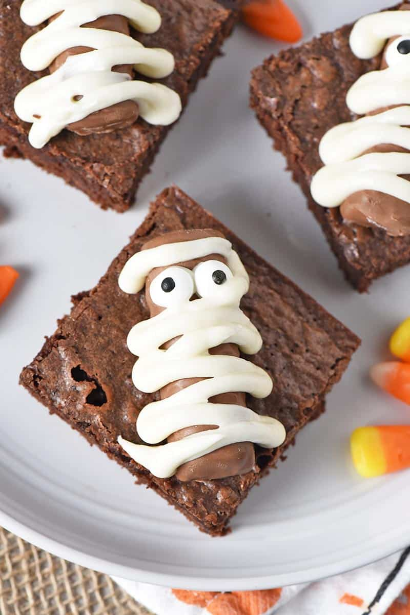 mummy halloween brownies made with Fun Size Twix bars on a plate with candy corn