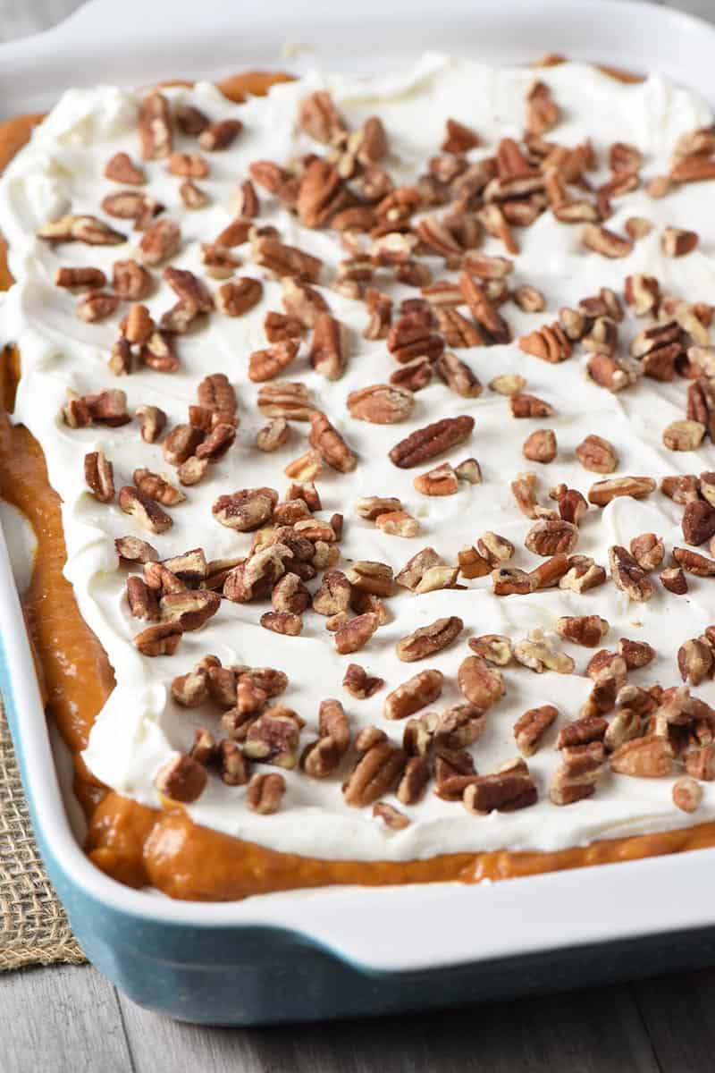 no bake pumpkin dessert layered in blue baking dish with pecans on top