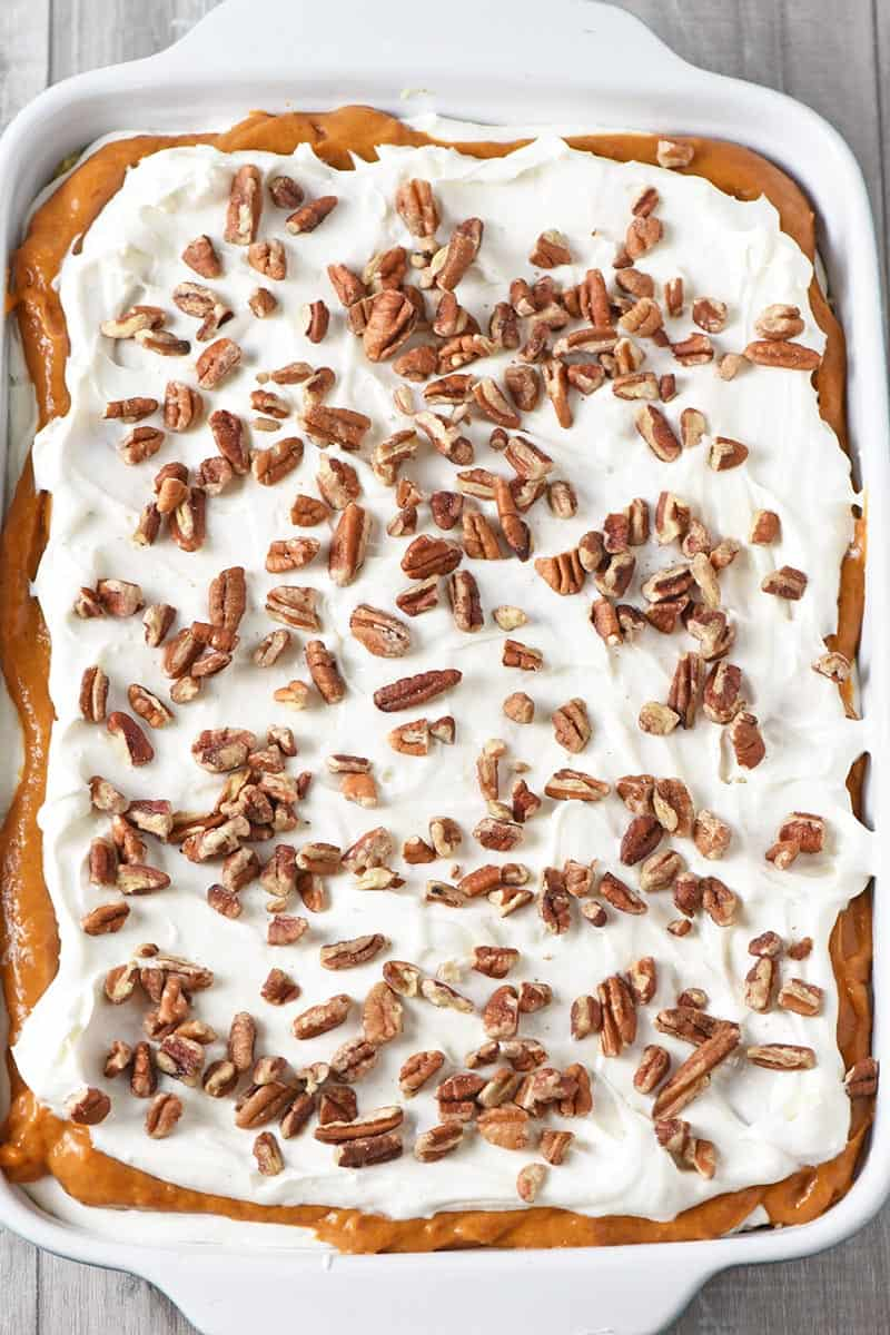 layered no bake pumpkin dessert recipe in blue baking dish with chopped pecans on top
