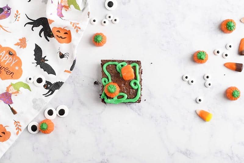 decorating pumpkin patch Halloween brownies with Brach's Mellowcreme Pumpkins and green icing for a quick and easy Halloween dessert