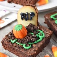 spooky graveyard brownies with Milano Cookies as gravestones, Oreos as dirt, green icing, and candy corn pumpkins