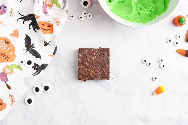square brownie for Frankenstein Halloween Brownies, with candy eyeballs and Wilton leaf green icing