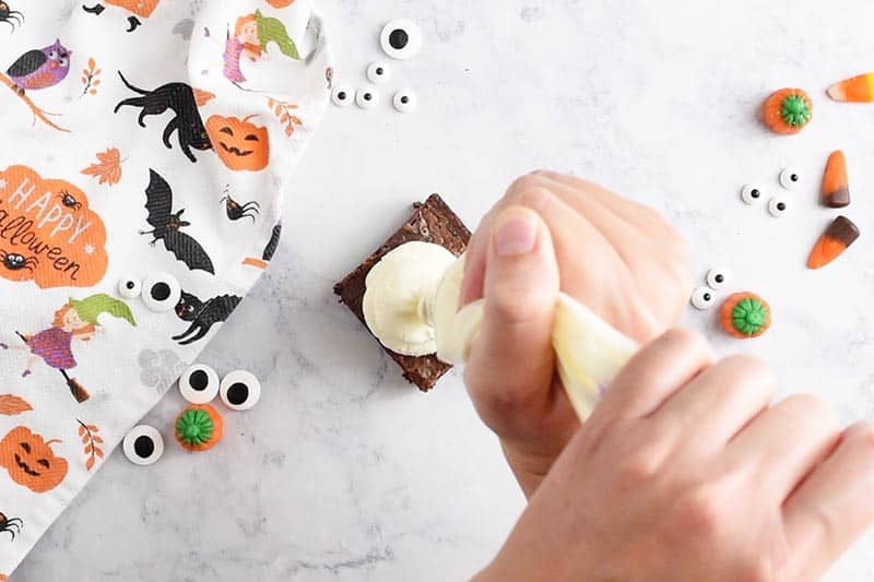 swirling whipped cream ghosts onto ghost halloween brownies with a pastry bag and Wilton Round Tip 2A, making easy halloween treats