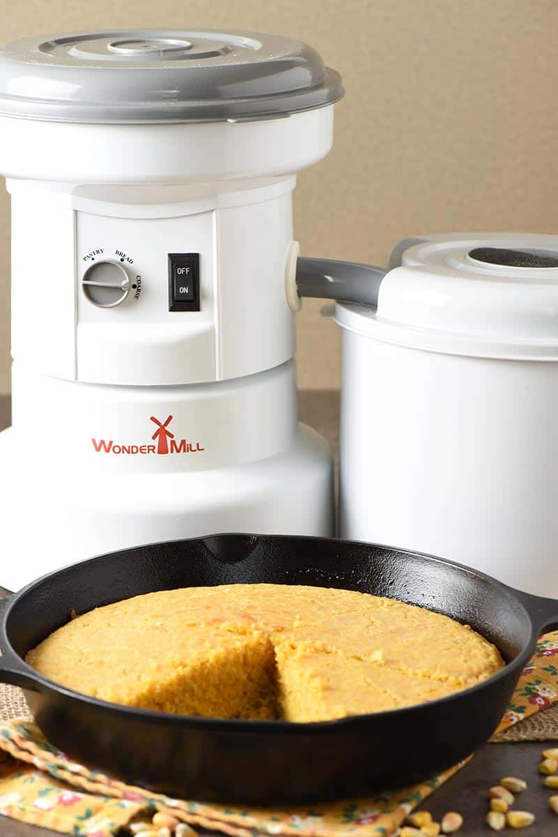 WonderMill grain mill with homemade buttermilk cornbread baked in cast iron skillet