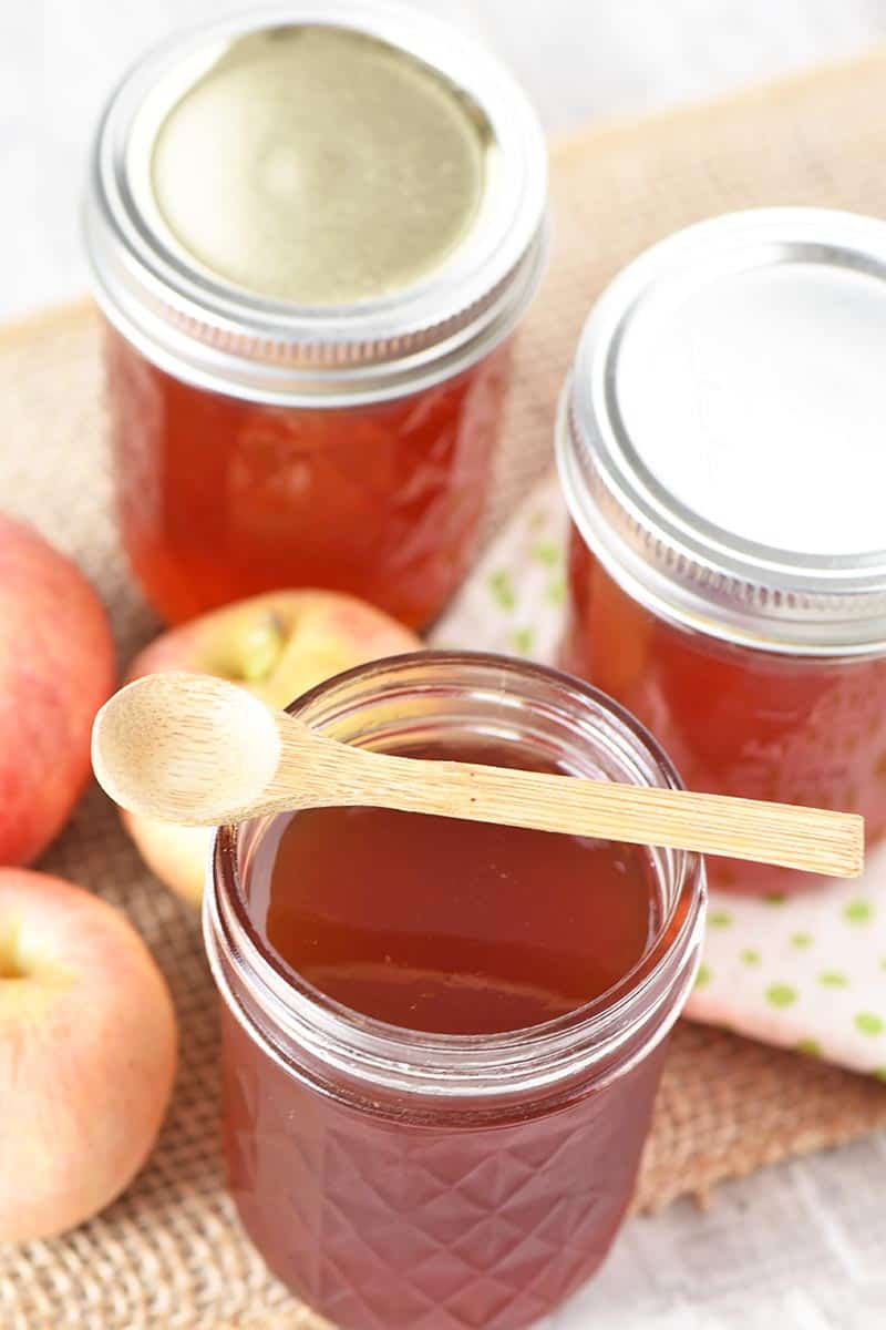 apple jelly in half pint jars with small wooden spoon and Gala apples