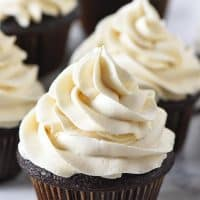 fluffy butterbeer buttercream frosting on dark chocolate cupcakes on white marble countertop